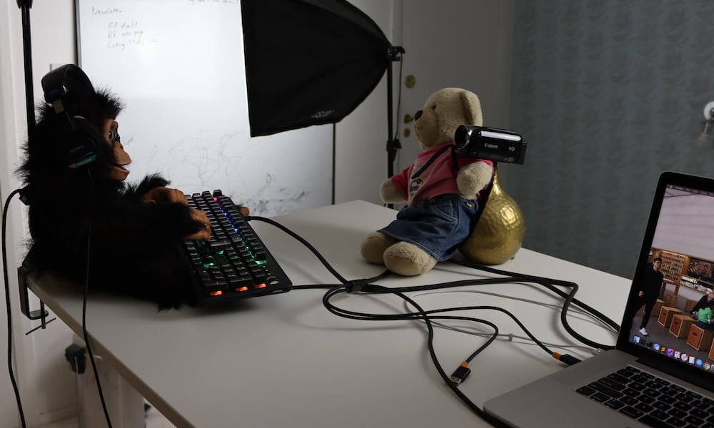 A chimpanzee types and wears headphones, while a teddy bear records him with a camcorder.